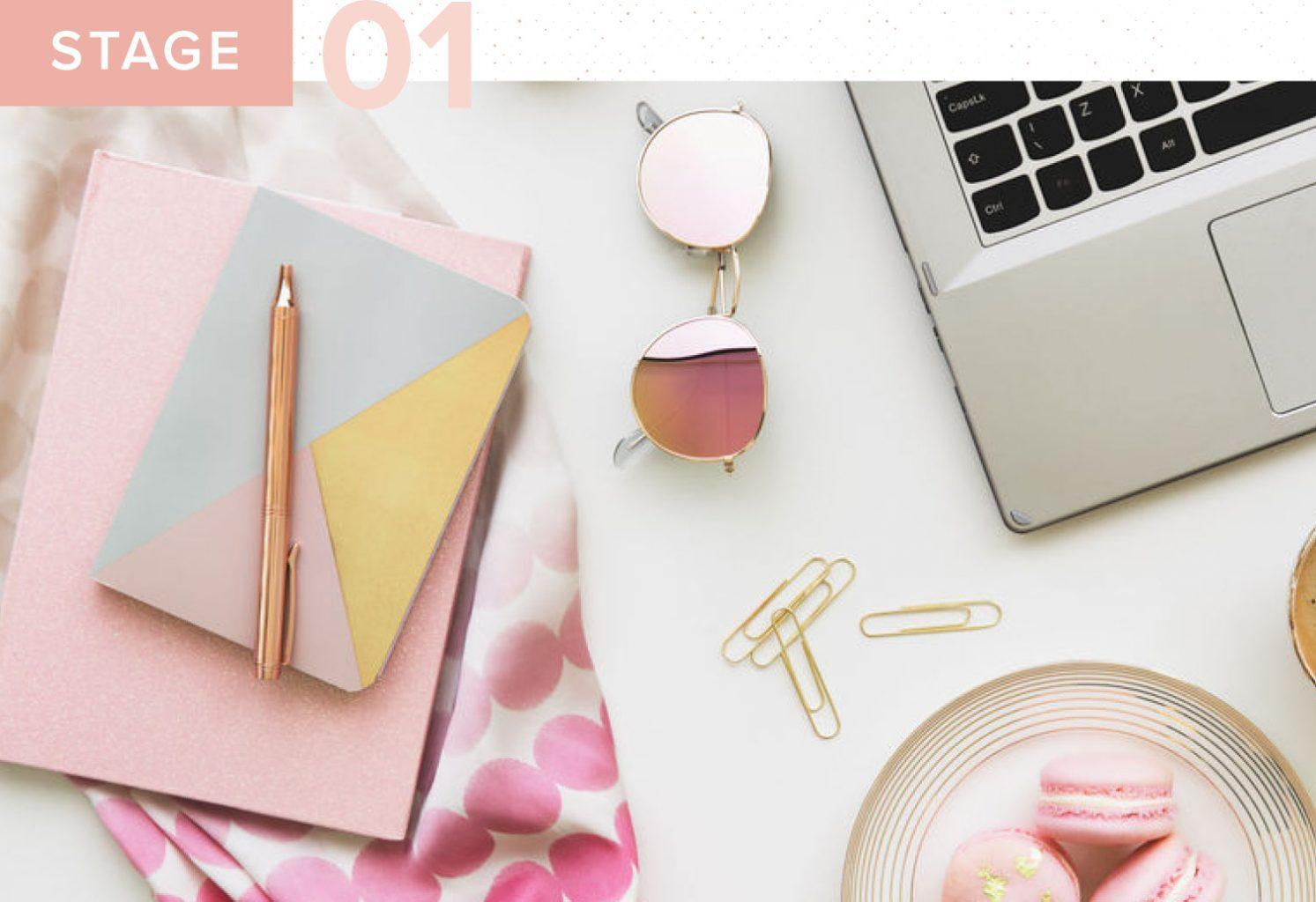 a desk with a pink notebook, pink sunglasses, macarons, and a laptop