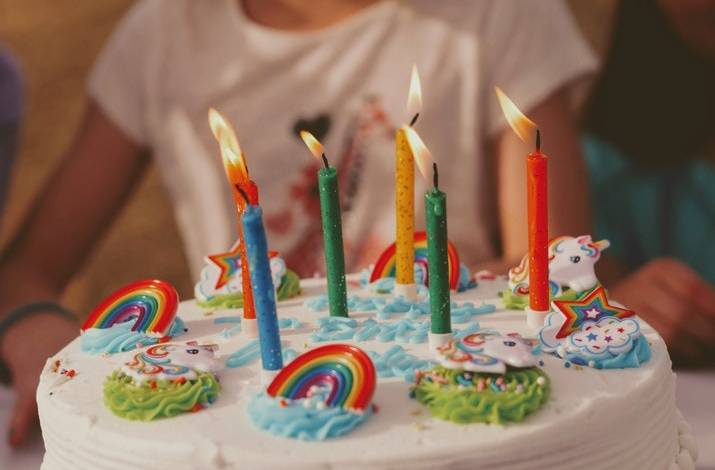 a child holding a birthday cake with candles