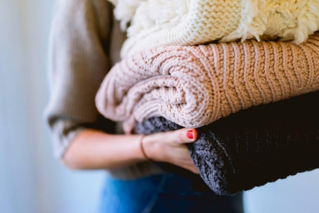 Woman carries a stack of knit blankets