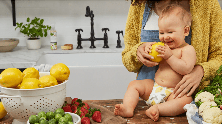 baby on a table delighted with a lemon
