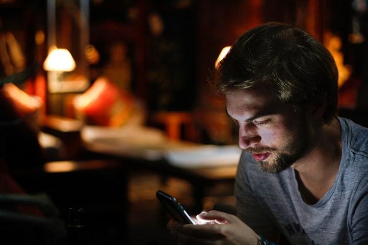 A man using his phone at night