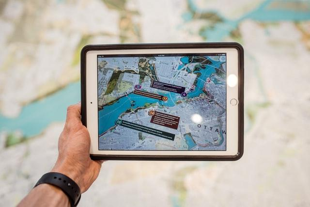 Hand holding a tab with a map on the screen
